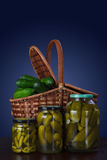 Canned cucumbers in jars and a basket of fresh cucumbers. 