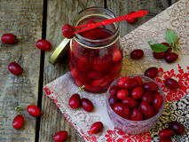 Canned of dogwood (cornelian cherry berry) on wooden background. Royalty Free Stock Photos