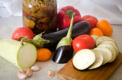Canned eggplant squash tomato garlic cutting board Royalty Free Stock Images