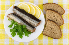 Canned fish, lemon, parsley and pieces of bread on tablecloth Royalty Free Stock Image