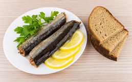 Canned fish with lemon and parsley in plate and bread Royalty Free Stock Photography