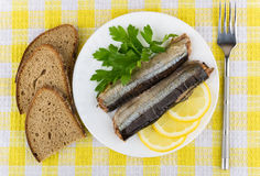 Canned fish, lemon, parsley in plate and pieces of bread. On tablecloth, top view Royalty Free Stock Photo