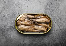 Canned fish in a tin. Close up and top view of smoked canned sardine in a tin over gray rustic concrete background. Tinned fish as a convenient, fast, healthy royalty free stock photo