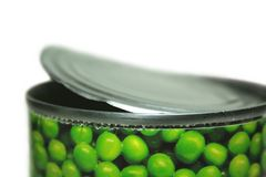 Canned food. Close-up of an opened can of peas against white background Stock Images