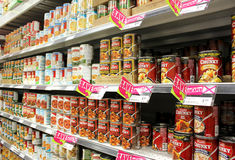 Canned food products in supermarket Stock Images