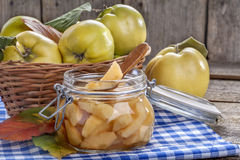 Canned and fresh quince. Canned fresh and healthy quince on an old wooden table Stock Photos