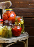 Canned fruits and vegetables in jars. On a wooden chair Stock Photos