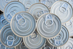 Canned goods stacked. Canned goods lids with pull rings Stock Photo