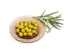 Green olives on saucer and olive branch Stock Photography
