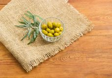 Green olives in small glass bowl and olive branch Stock Images
