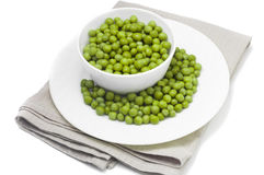 Canned green peas. On white plate and linen napkins, white background Stock Photos