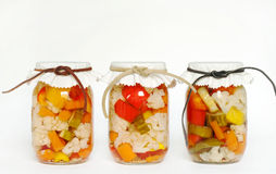 Canned Homegrown Pickled Vegetables. Canned, homegrown, organic vegetables consisting of cauliflower, carrots, red, orange & yellow peppers & pickles preserved stock photos