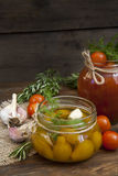 Canned marinated tomatoes in tomato juice on a wooden table Royalty Free Stock Image