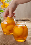 Canned natural vegetarian peaches in glass jars with compote Stock Photography