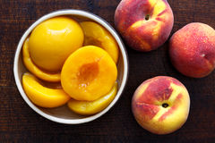 Canned peach halves in bowl on dark background with whole fresh. Peaches. From above royalty free stock photography