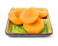 Canned peach halves in plate. Isolated on white background stock images