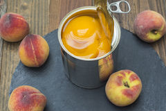 Canned peaches. Tin can with preserved peaches, fresh peaches around the can Royalty Free Stock Photos