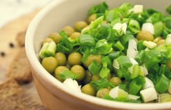 Canned peas with chives in ceramic bowl on wooden background. He Royalty Free Stock Photo