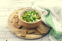 Canned peas with chives in ceramic bowl on wooden background. He Stock Image