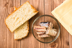 Canned sardines in a bowl and pieces of white bread on a wooden background Royalty Free Stock Image