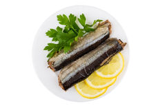Canned saury with lemon and parsley in glass plate Stock Photos