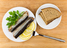 Canned saury with lemon and parsley in glass plate Stock Photography