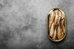 Canned smoked fish. Close up and top view of smoked canned sardine in a tin over gray background, space for text. Tinned fish as a convenient, fast, healthy food stock photography