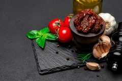 Canned Sundried or dried tomato halves in wooden bowl. Dark concrete background Stock Images