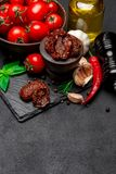Canned Sundried or dried tomato halves in wooden bowl. Dark concrete background Royalty Free Stock Image