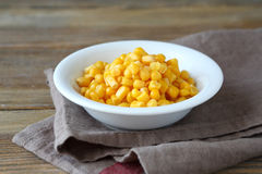 Canned sweet corn in a bowl. Food on a wooden background Stock Photography