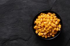 Free Canned Sweet Corn In A Black Ceramic Bowl Isolated On Black Slate. Top View. Space For Text Stock Photography - 161160312