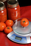 Canned Tomatoes. And a kitchen scale shot against a red background Stock Photos