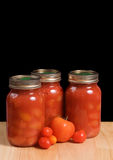 Canned Tomatoes. Three mason jars filled with canned tomatoes shot on a wooden board and isolated against a black background Stock Photos
