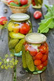 Canned tomatoes, cucumbers and garlic in glass jar Stock Photography