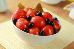 Canned tomatoes with olives in a dish Royalty Free Stock Image