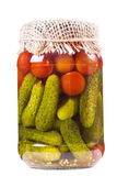Canned tomatoes and pickled cucumbers in glass jar Royalty Free Stock Image