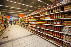 Canned tomatoes on the shelves of a supermarket Royalty Free Stock Photography