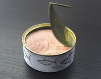 Canned tuna. Fresh and soft canned tuna on the wooden table, with breadstick and can royalty free stock images