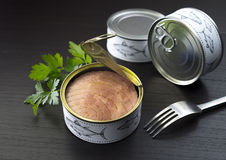 Canned tuna parsley and fork. Fresh and soft canned tuna on the wooden table, with breadstick and can royalty free stock photography