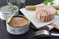Canned tuna on the plate. Fresh and soft canned tuna on the wooden table, with breadstick and can stock images