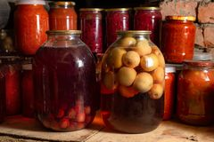 Canned vegetables in transparent glass jar. Apple compote in large transparent jars. Homemade canned juice royalty free stock photos