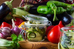 Canned zucchini and fresh vegetables Royalty Free Stock Images