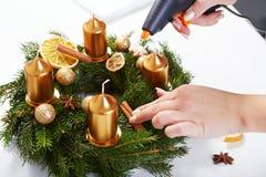 Cannella degli addetti della donna su una corona di Natale Fotografia Stock Libera da Diritti