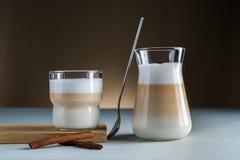 Cannella di vetro moderna delle tazze del caffè del Latte su fondo scuro marrone blu immagini stock