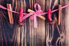 Cannella e anises d'attaccatura su una corda su un fondo di legno Immagine Stock Libera da Diritti