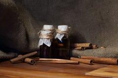 Cannelle moulue, huile essentielle et cannelle de bâtons de cannelle sur un fond en bois de darck Photographie stock