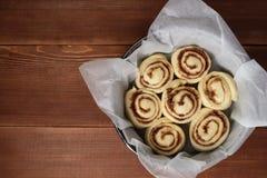 Cannelle Rolls Petits pains de cannelle fraîchement cuits au four avec les épices et le cacao remplissant sur le papier parchemin image libre de droits