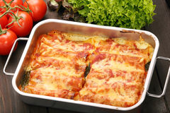Cannelloni baked in a roasting pan on a wooden background Royalty Free Stock Photos