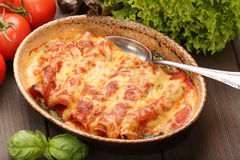 Cannelloni baked in a roasting pan on a wooden background Royalty Free Stock Image