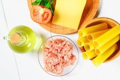 Cannelloni italiano da massa O tubo cru para encher o enchimento cercado por ingredientes para cozinhar, queijo parmesão, tomate, imagens de stock royalty free